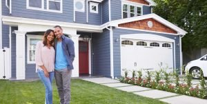 Couple standing on lawn of new home purchase